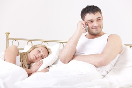 cheating: couple in bed - man cheating while a woman sleeping Stock Photo