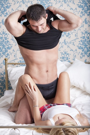 Loving couple in bed - man undressing underwear Stock Photo - 13137015