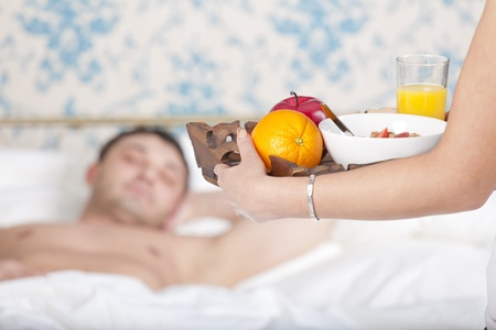 woman serving breakfast for man to bed at home photo