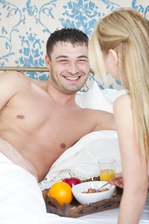 happy couple with breakfast in bed photo