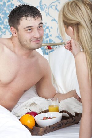 happy couple having breakfast together in bed photo