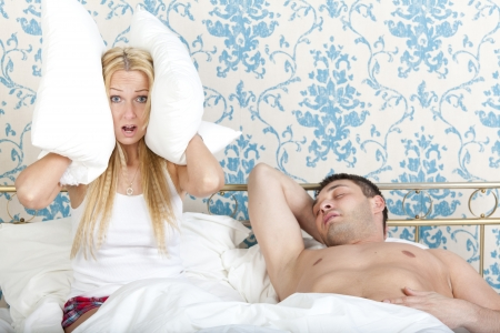 Woman trying to sleep while man snoring photo