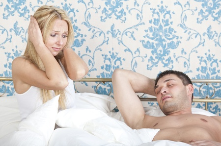 frustrated woman on the bed and snoring man sleeping photo