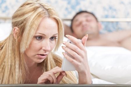 enamorados en la cama: problema de pareja - mujer que lee un mensaje en el tel�fono de su amante Foto de archivo