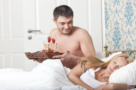man serving breakfast to bed with two glasses sparkling wine photo