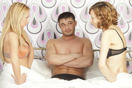 man sitting between two frustrated women in bed - focus on man Stock Photo - 13136971
