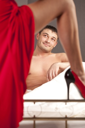 woman in stiletto seducing man in bed Stock Photo