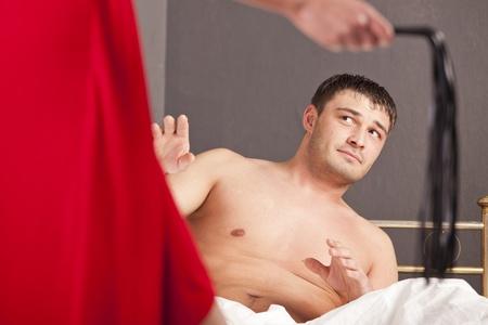 dominacion: hombre en la cama ha sido dominado por una mujer con un l�tigo Foto de archivo
