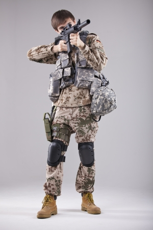 Soldier in camouflage aiming with machine gun in a white studio photo