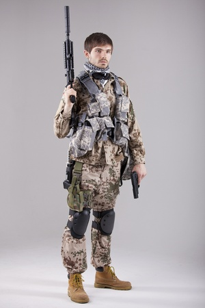Portrait of Armed Soldier with two guns in a white studio photo