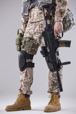 armed soldier with machine gun in white studio photo