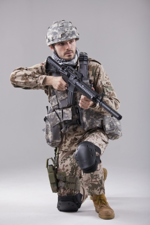 man with gun: Kneeling Soldier with machine gun in studio Stock Photo