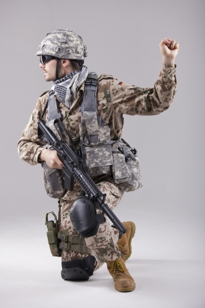 armed soldier kneeling with hand warning or stop gesture photo