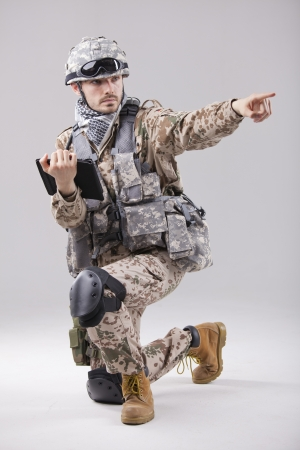 Soldier or commander holding tablet computer and pointing with a finger