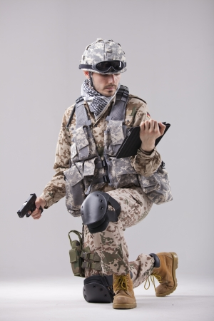 Modern soldier with handgun and tablet computer photo