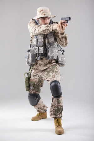 Soldier in camouflage uniform with a handgun aiming - shot in white studio photo