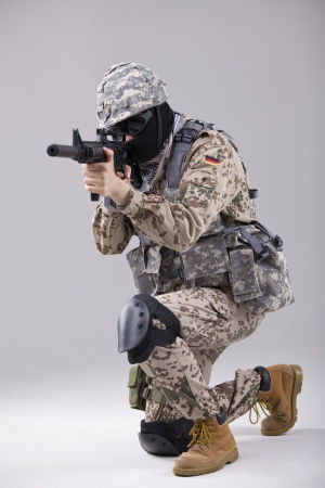 Soldier special forces with machine gun in a white studio photo