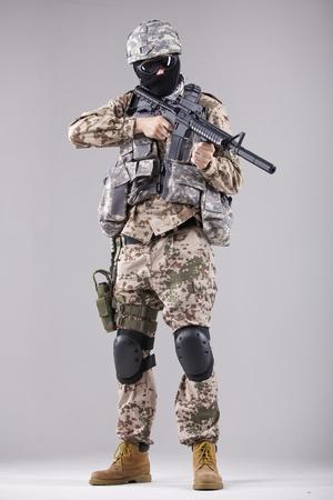 soldado: Militar, terrorista o un soldado con uniforme de camuflaje con una ametralladora