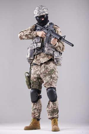 balaclava: Military man, terrorist or soldier in camouflage with machine gun