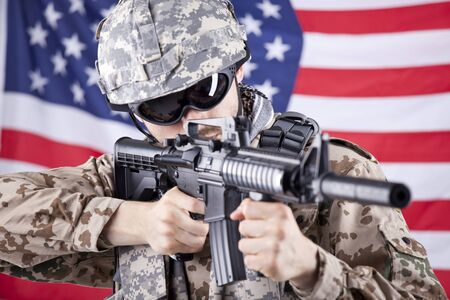 American soldier shooting or aiming - american flag waving in background photo