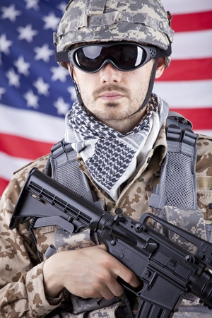 Portrait of armed american soldier in camouflage over american flag photo