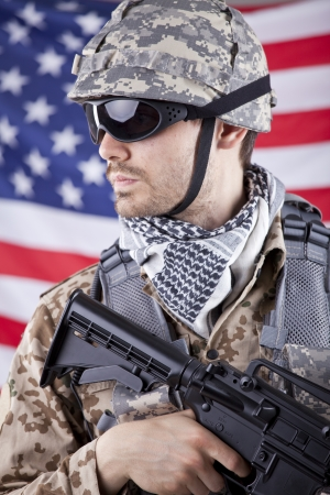 American soldier in camouflage with machine gun over american flag photo