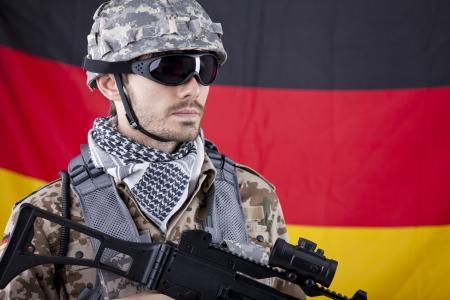 NATO Soldier with machine gun and helmet over german flag photo