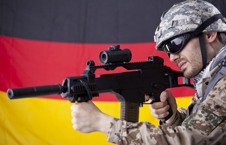 German soldier with machine gun aiming or shooting - german flag in background photo