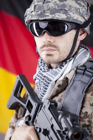 German soldier in camouflage with machine gun over german flag photo