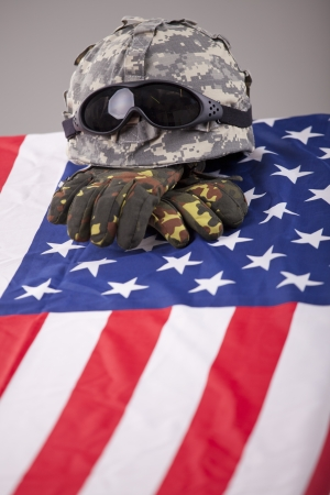 a memorial to fallen soldiers: Military funeral - helmet and gloves on the american flag Stock Photo