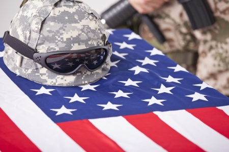 Military funeral - helmet on the american flag and soldier in the background