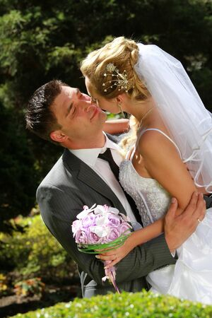Embracing wedding couple in the park photo
