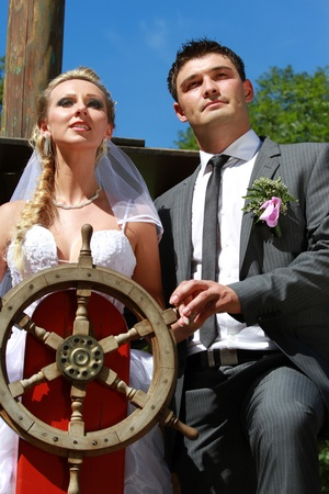 wedding couple on the antique ship with wooden steering wheel photo