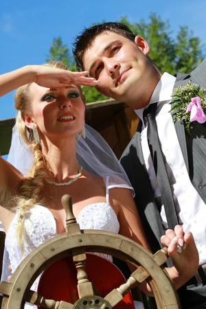portrait of wedding couple with ship steering wheel photo