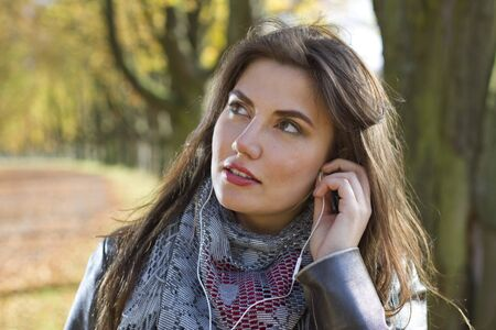 woman in park listening music in earphones Stock Photo - 15895537