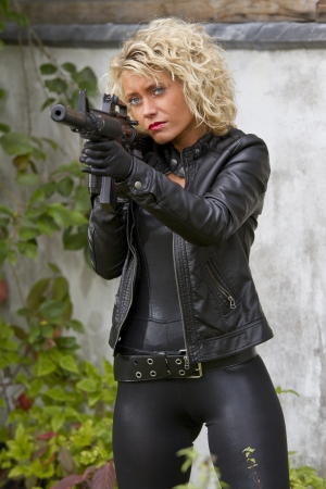 Sexy female agent with silencer machine gun outdoor photo