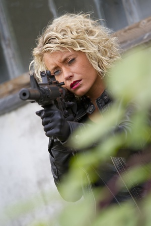female spy with machine gun and silencer aiming  photo