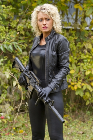 catsuit: Woman clad in leather outfit standing with a machine gun outdoor