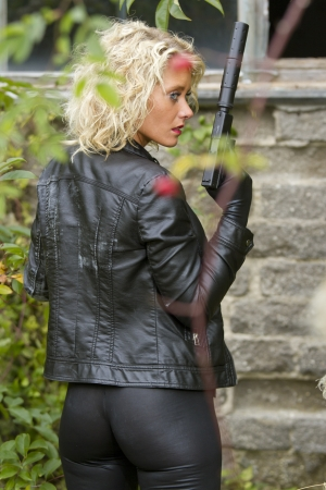 catsuit: Leather clad woman holding a silencer gun outdoor - playing a agent