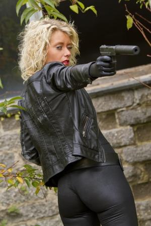 ljuddämparen: Sexy Secret kvinnlig agent siktar med ljuddämpare pistol