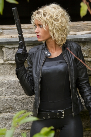 Woman in leather catsuit and gloves with a silencer gun - outdoor Stock Photo