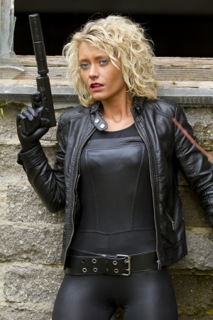 Female spy in leather dress standing at the wall, holding a silencer gun in the hand  Fear expression on her face