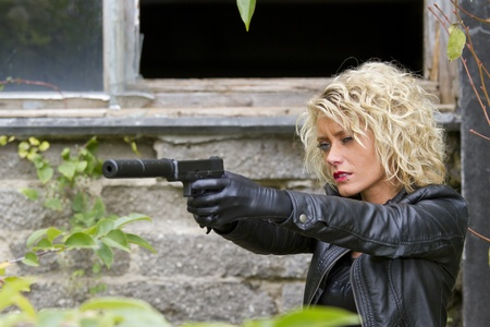 Female Spy with a silencer handgun aiming outdoor