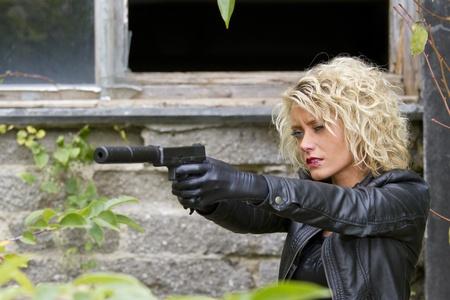 ljuddämparen: Kvinna Spy med ljuddämpare pistol syftar utomhus Stockfoto