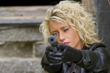 the silencer: woman with a silencer gun aiming in the camera - focus on the face  Stock Photo