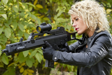 war crimes: woman with a machine gun outdoor