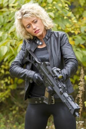 ljuddämparen: Sexig kvinna i läder med ett maskingevär - utomhus Stockfoto