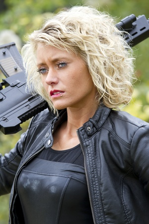Portrait of cute woman in leather with machine gun outdoor photo