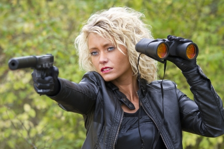 dangerous cute woman with a silencer gun and binoculars outdoor photo