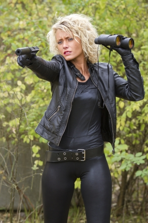 silencer: Woman in leather outfit shooting from a silencer handgun - outdoor Stock Photo